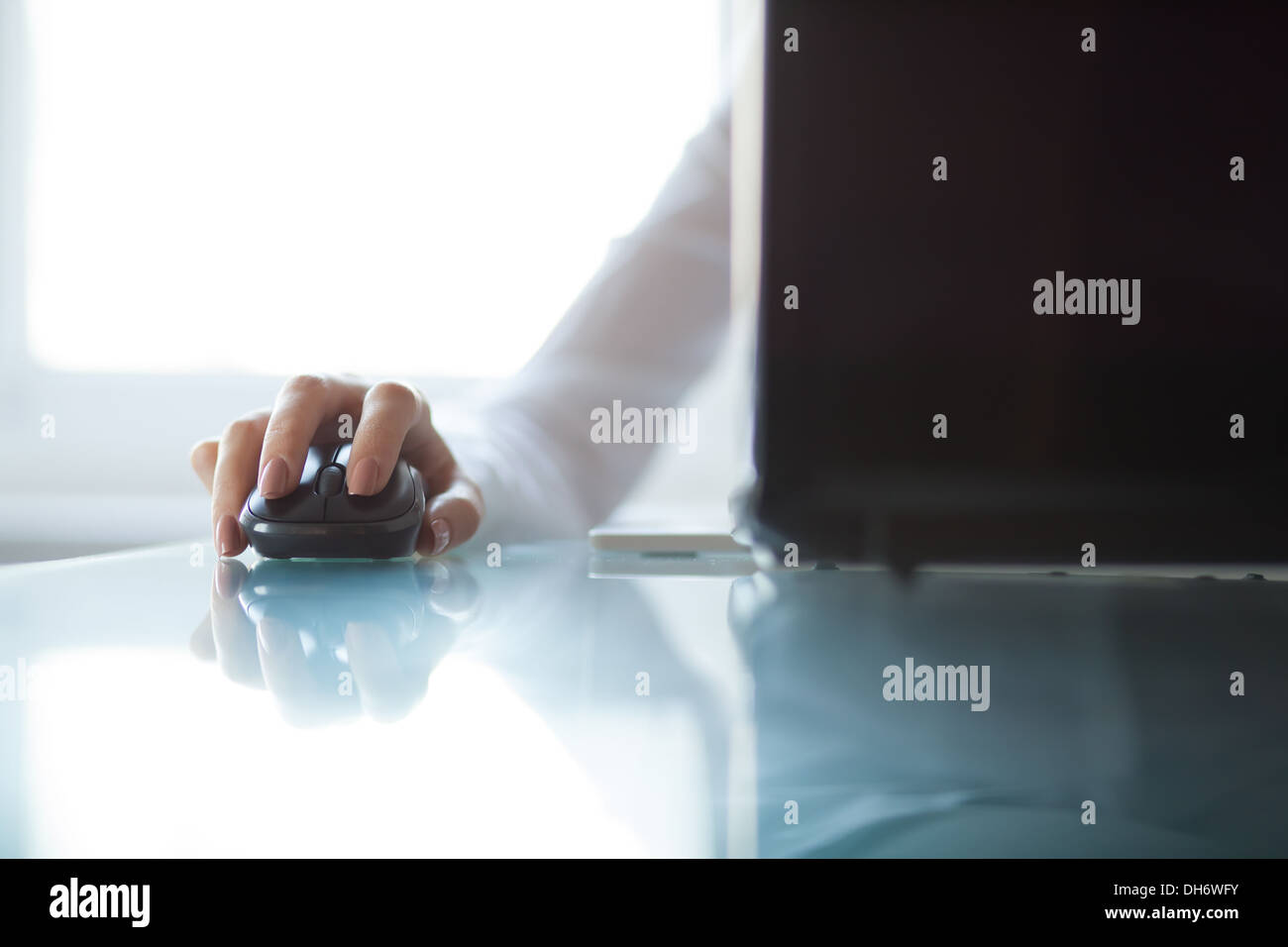 Woman's hand using cordless mouse on glass table Stock Photo