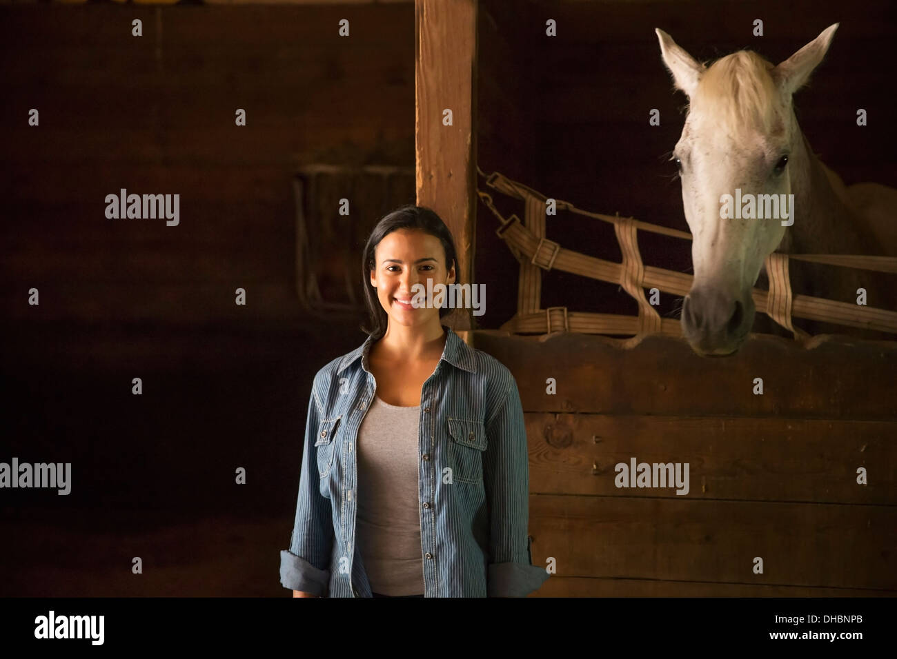 An organic farm in the Catskills. A woman standing in a stable, with a white horse looking over the stall. - Stock Image