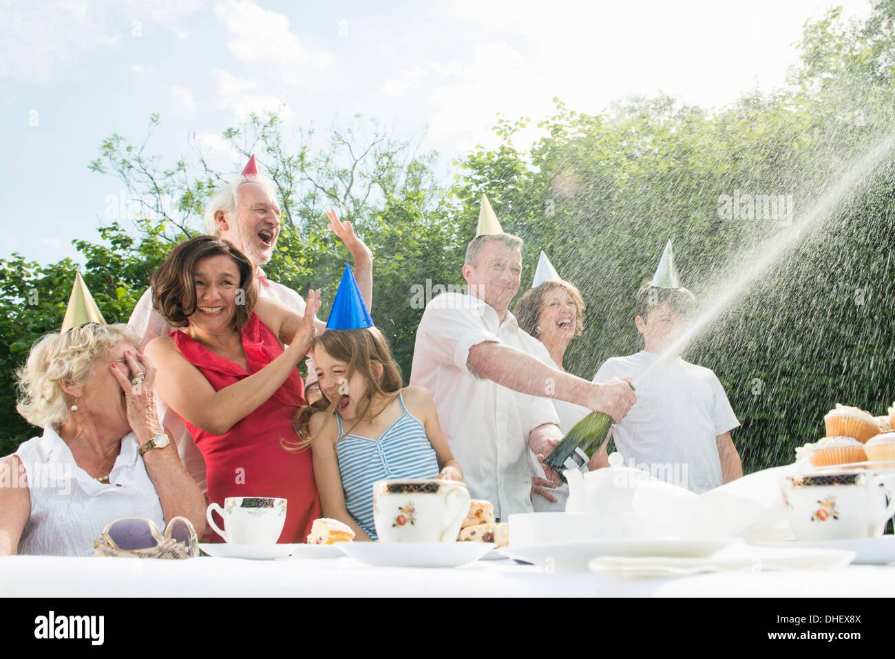 Family celebrating birthday, man opening champagne - Stock Image