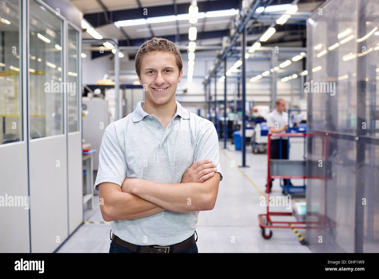 Portrait of worker with arms folded in engineering factory - Stock Image