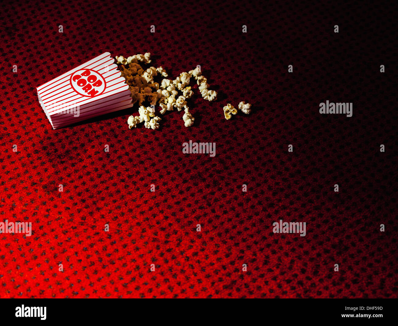 Spilled carton of popcorn on cinema carpet - Stock Image