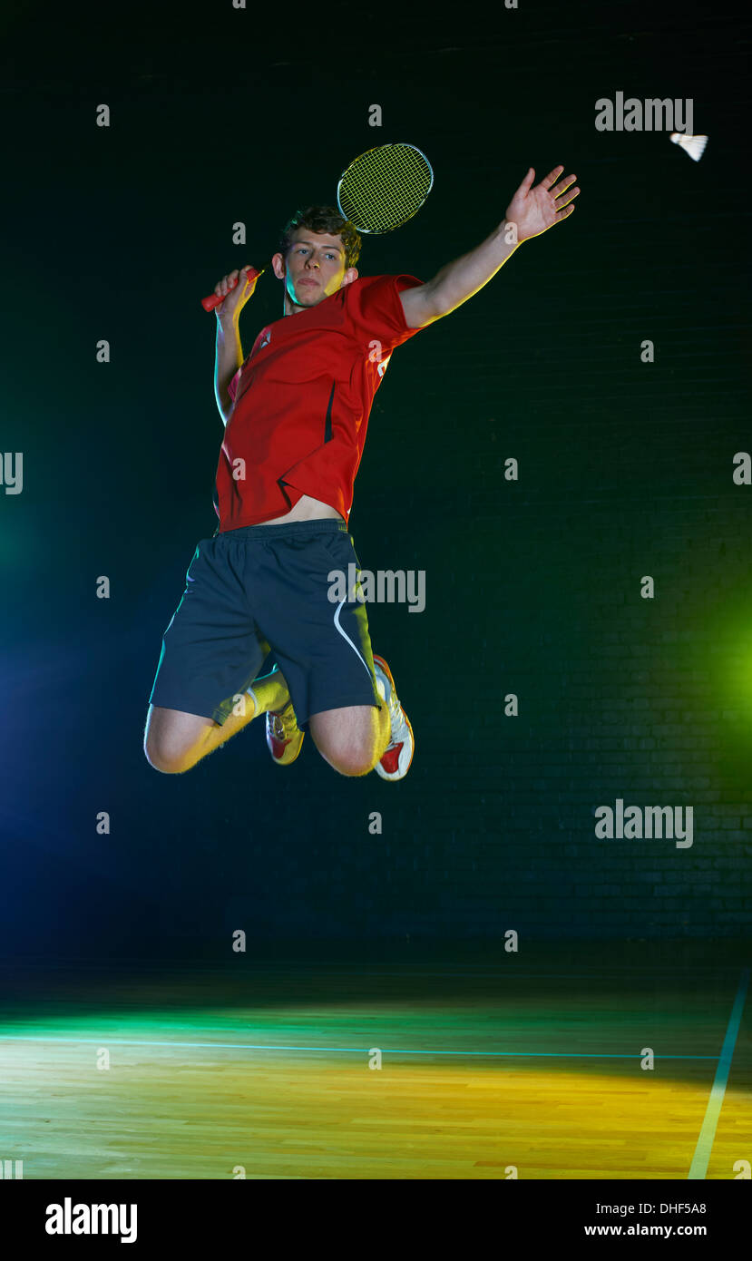 Young male badminton player mid air on court - Stock Image