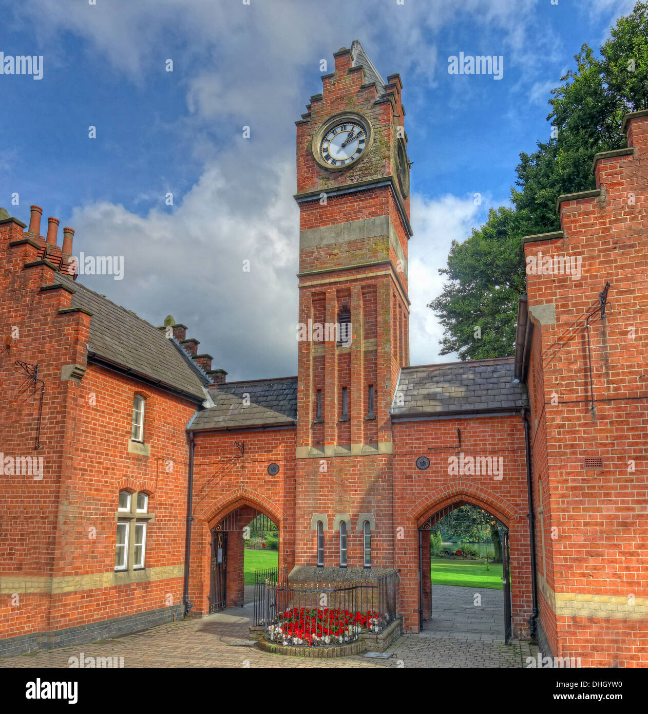 West,Midlands,England,UK,famous,clock,tower,clocks,timepiece,time,piece,gate,entrance,port,portal,red,brick,flowers,summer,best,loved,parks,saddlers,saddler,things,to,see,in,tourist,tourism,attraction,lodge,fine,old,victorian,building,gotonysmith,buildings,flanking,bays,contain,gates,below,a,depressed,gothic,arch,and,slate,saddle-back,roof,linking,to,two,storey,bays,below,a,stepped,gable,with,stone,dressed,tripartite,windows.,Chimney,stacks,are,at,the,extremities,with,that,on,the,right,showing,its,original,crenellated,pot.,Low,single,storey,end,bays,stand,below,slate,saddlebacks,with,stepped,gable,ends,and,double,lancets,stone,dressed,Black,Country,Buy Pictures of,Buy Images Of,Black Country,Walsall Black Country
