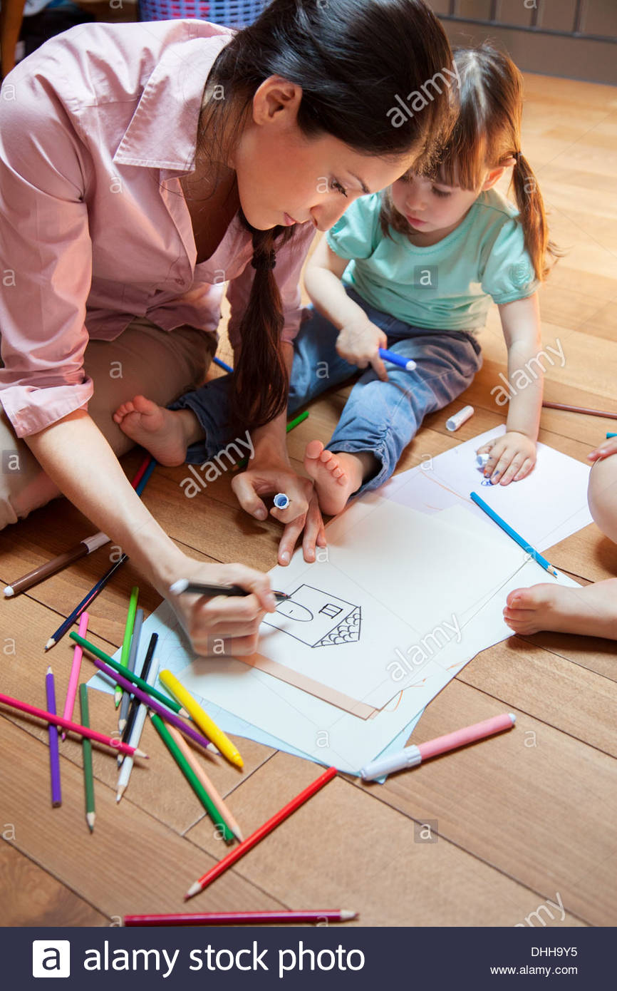 Mother and daughter drawing picture of house - Stock Image