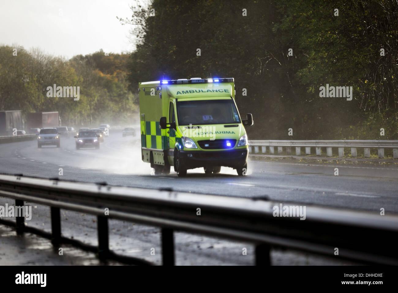 British ambulance on a UK motorway - Stock Image