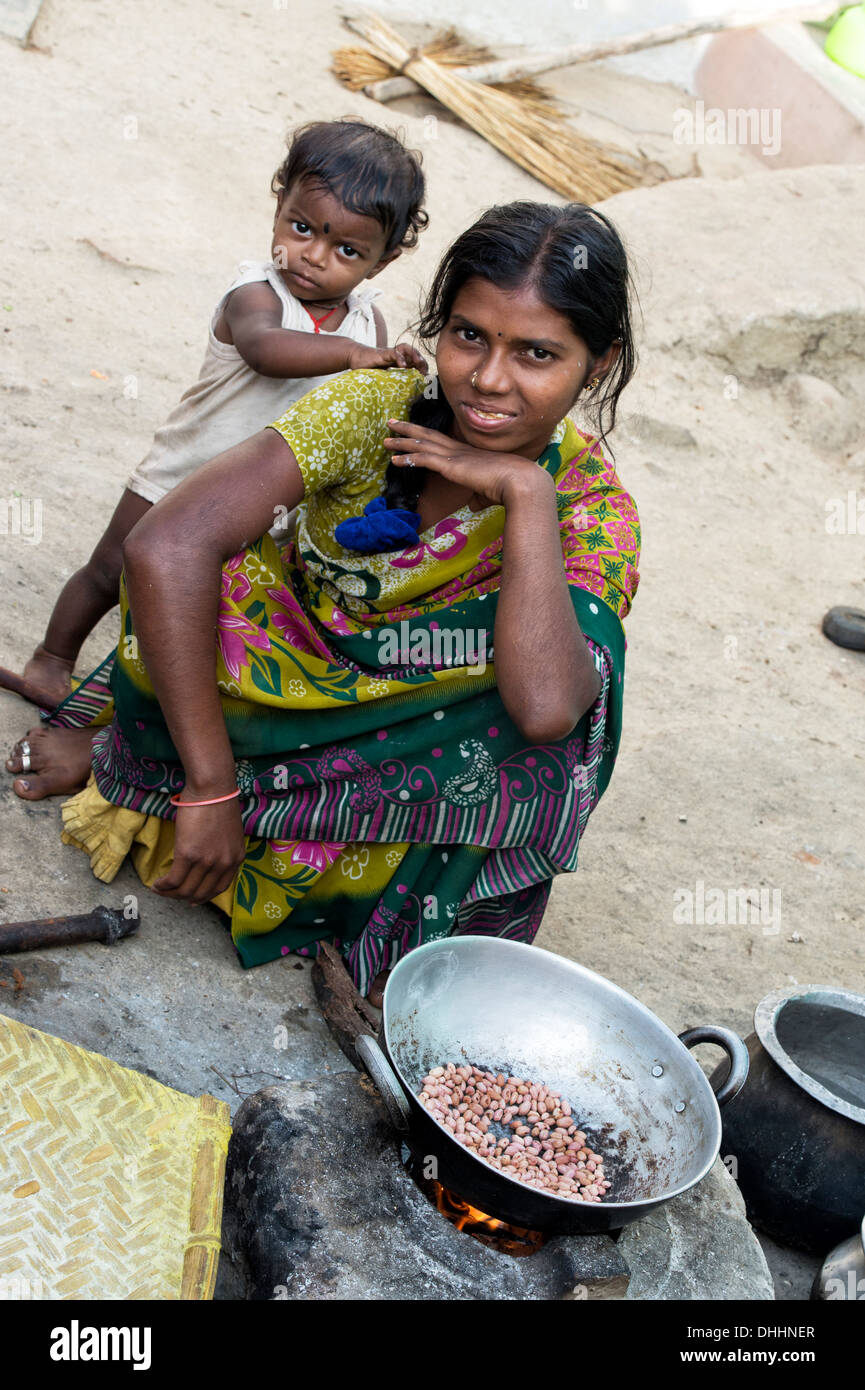 Indian teenage girl and child cooking peanuts on an open fire outside her home in a rural village. Andhra Pradesh, - Stock Image
