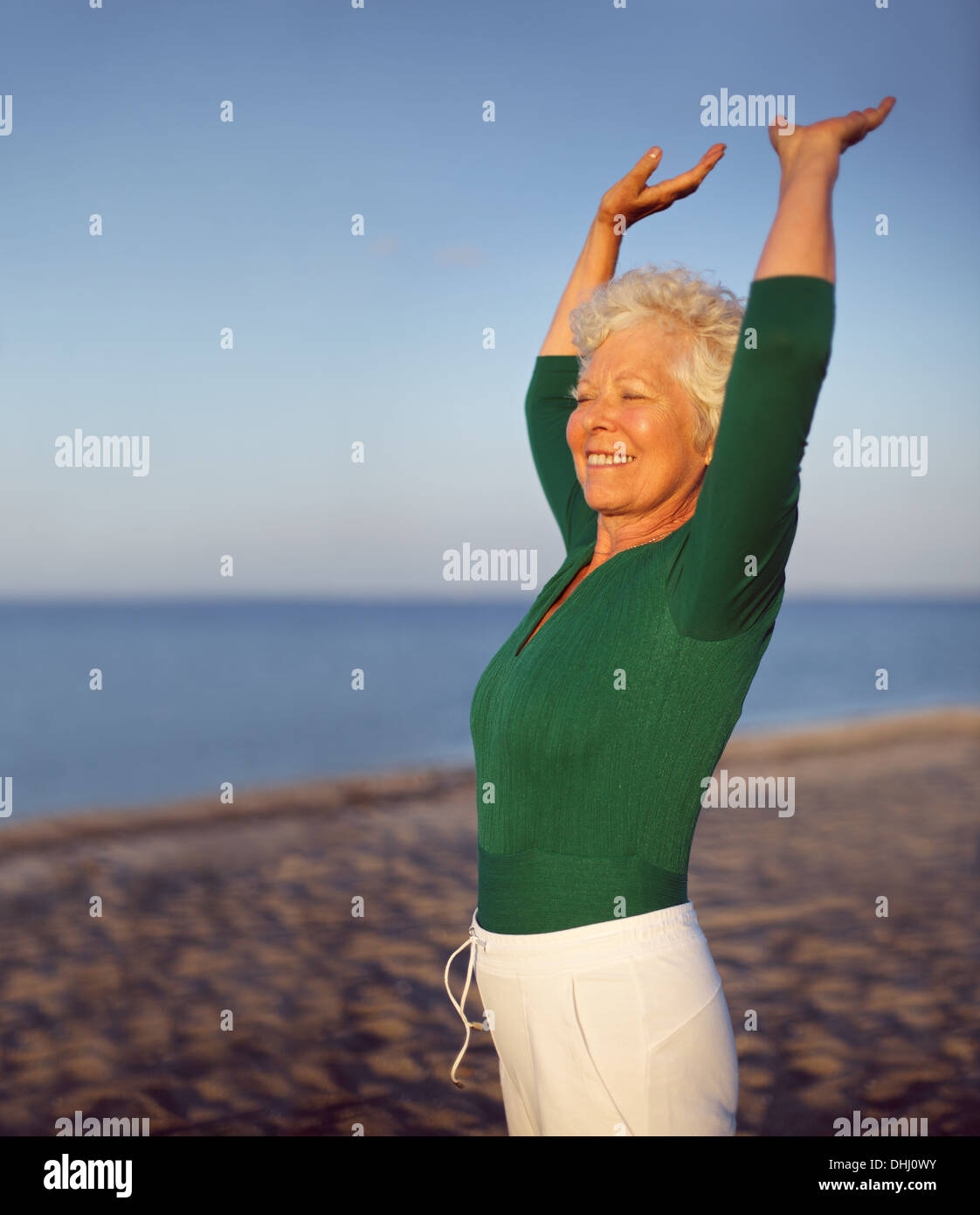 Portrait of beautiful mature woman practicing yoga on beach with copyspace. Old caucasian woman exercising outdoors - Stock Image