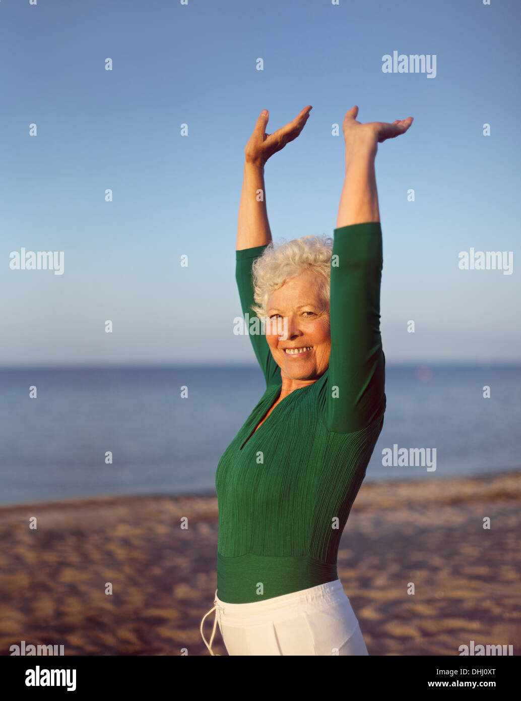 Portrait of healthy senior woman practicing yoga on beach with copyspace. Old caucasian woman exercising outdoors - Stock Image