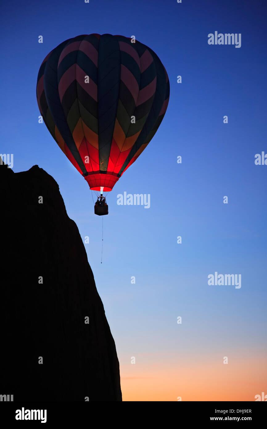 Hot air balloon near bluff, 'Dawn Patrol' event, Red Rock Balloon Rally, Gallup, New Mexico USA - Stock Image