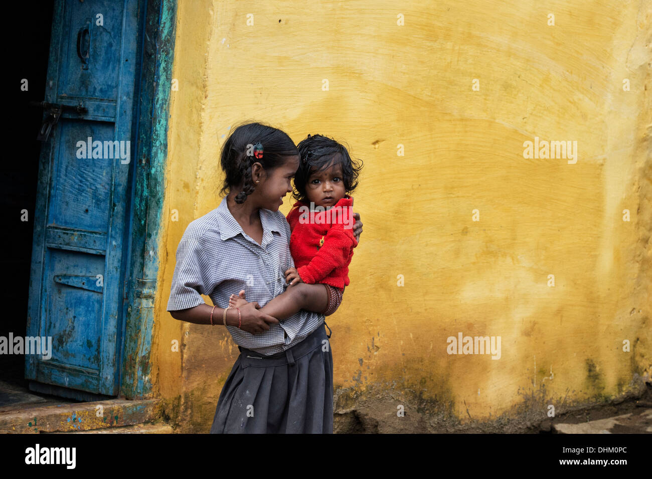 Young Indian girl holding her baby sister on her hip in a rural indian village. Andhra Pradesh, India - Stock Image