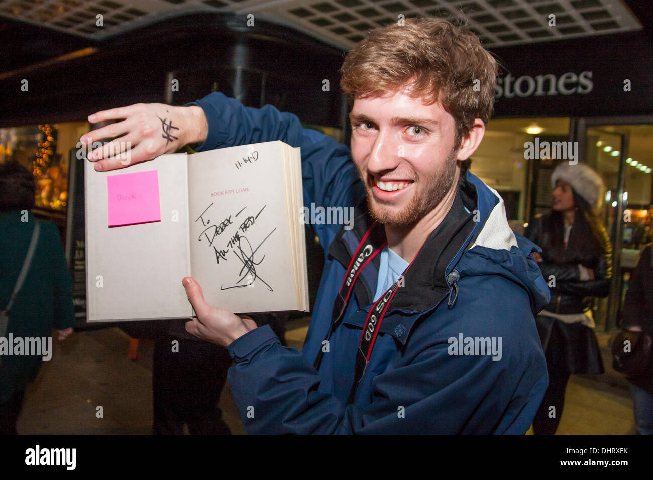 London, UK. 14th November 2013. A happy fan displays his signed copy of JJ Abrams book, Doug Dorst, outside Waterstones - Stock Image