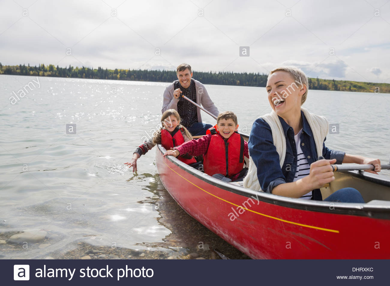 Happy family canoeing on lake - Stock Image