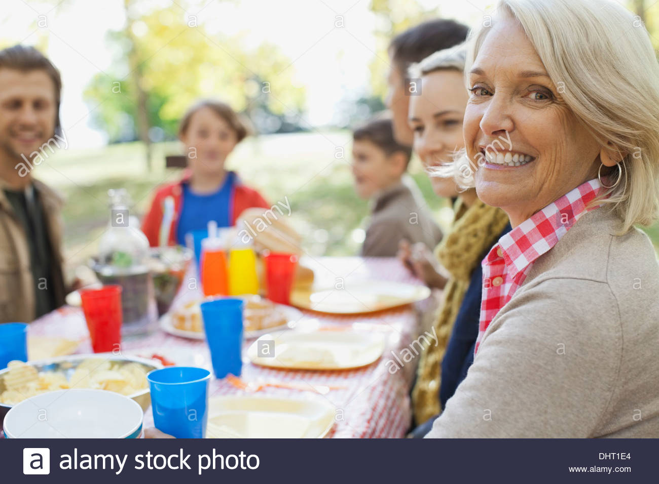 Portrait of happy mature woman with family at dining table in park - Stock Image