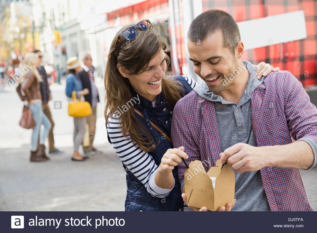 Smiling couple sharing a meal from a food truck - Stock Image
