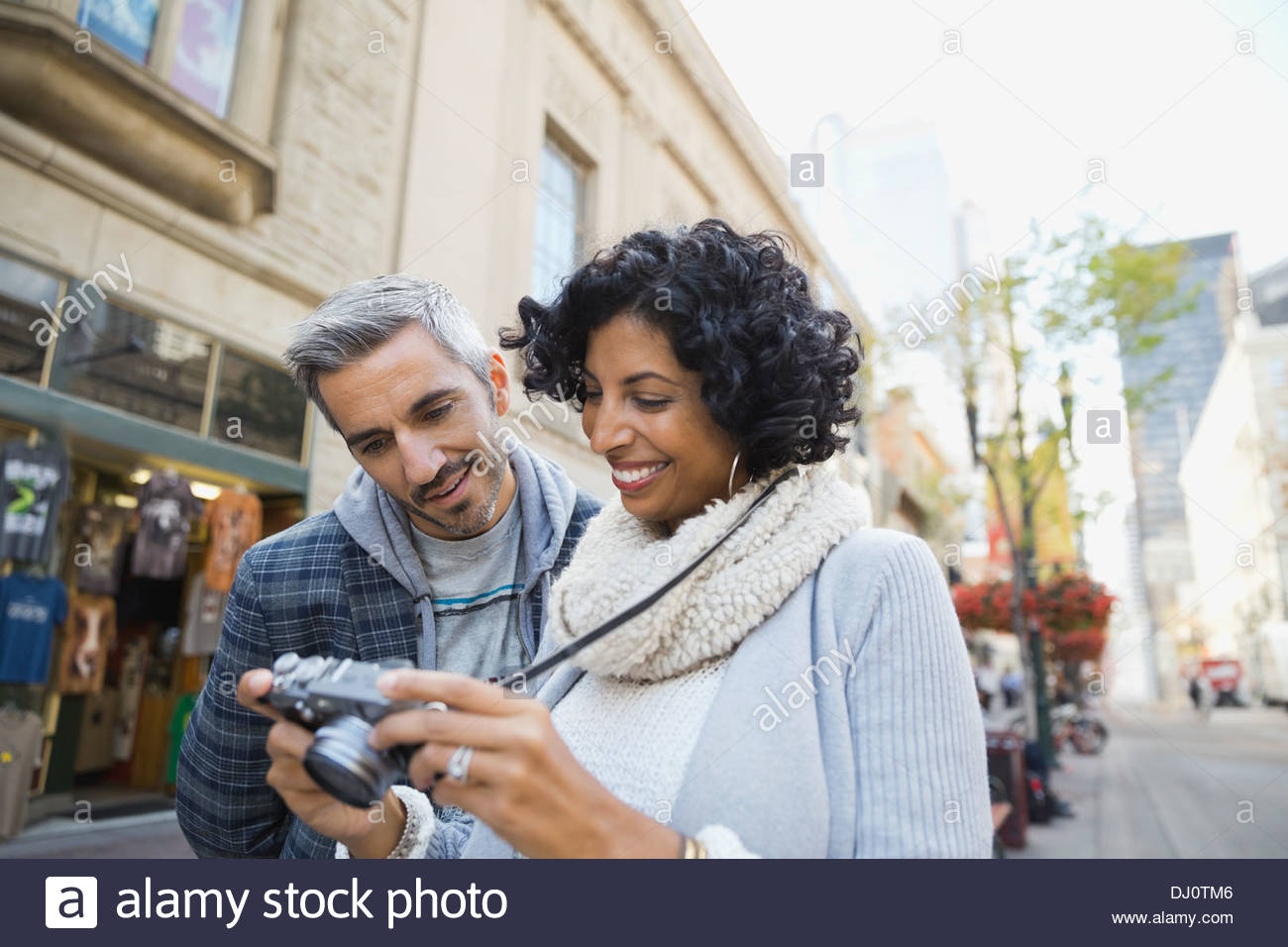 Couple looking at digital camera on city street - Stock Image