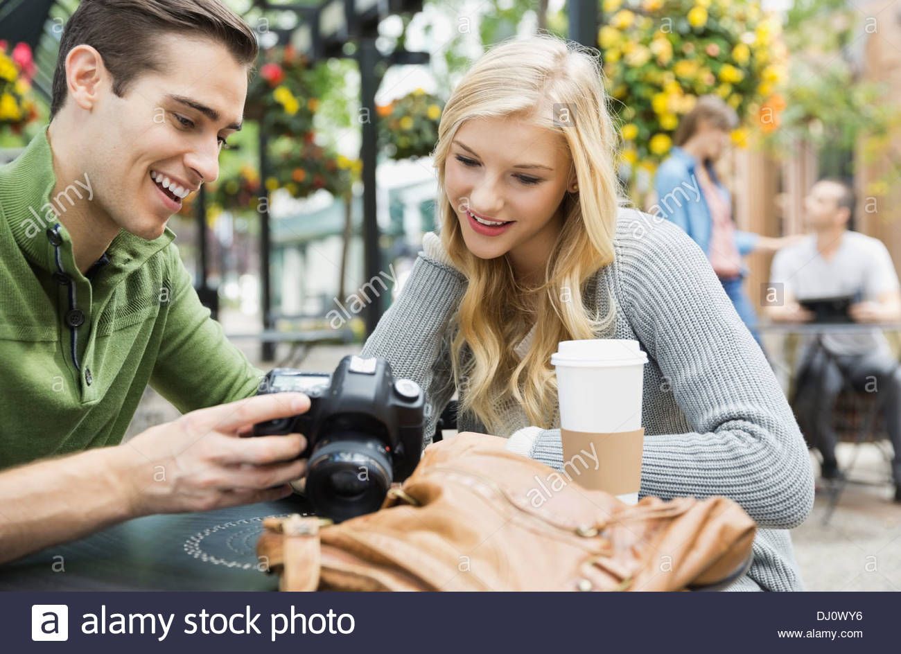 Man showing photographs on camera to woman - Stock Image