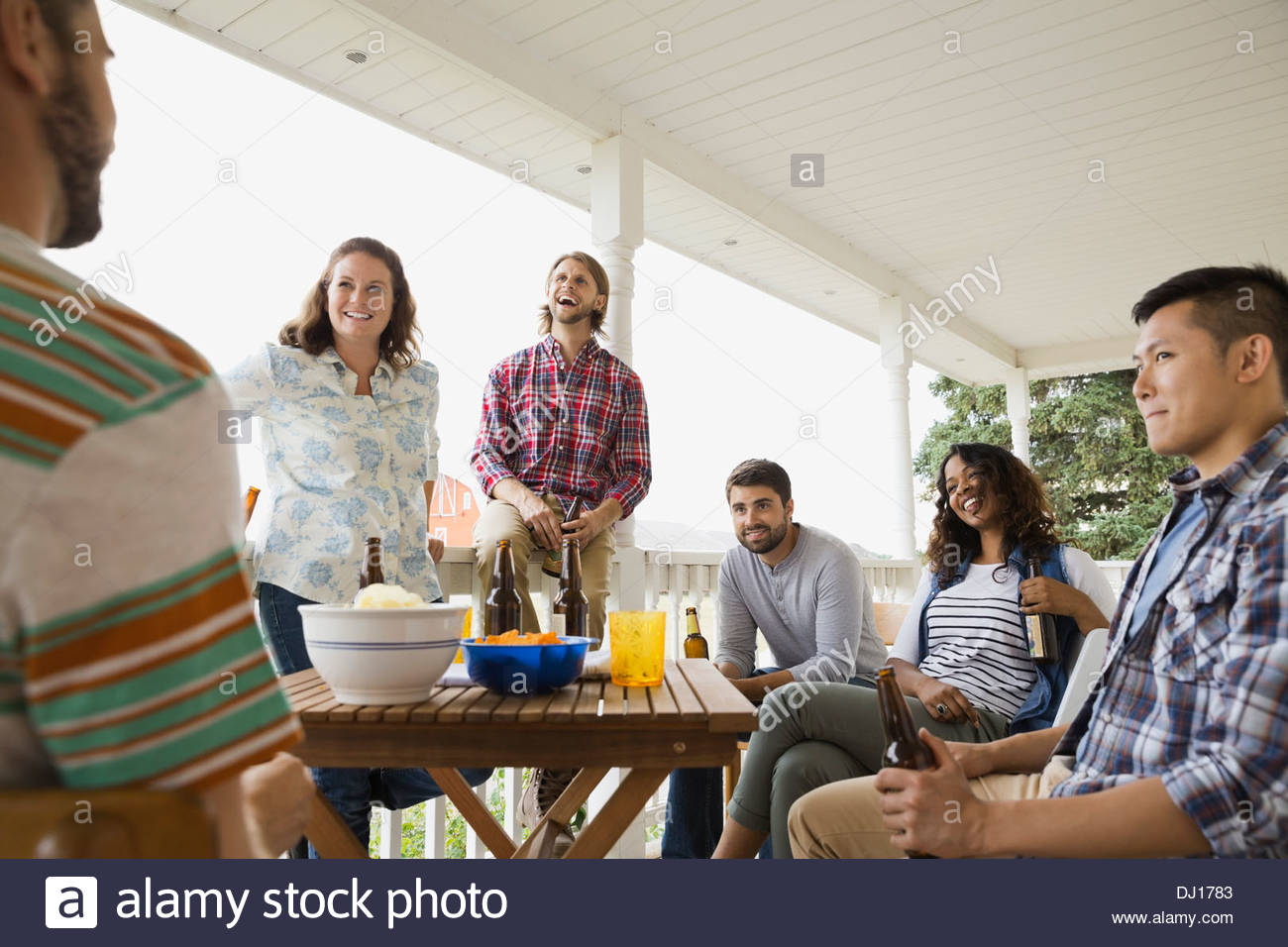 Multiethnic friends enjoying drinks on porch - Stock Image