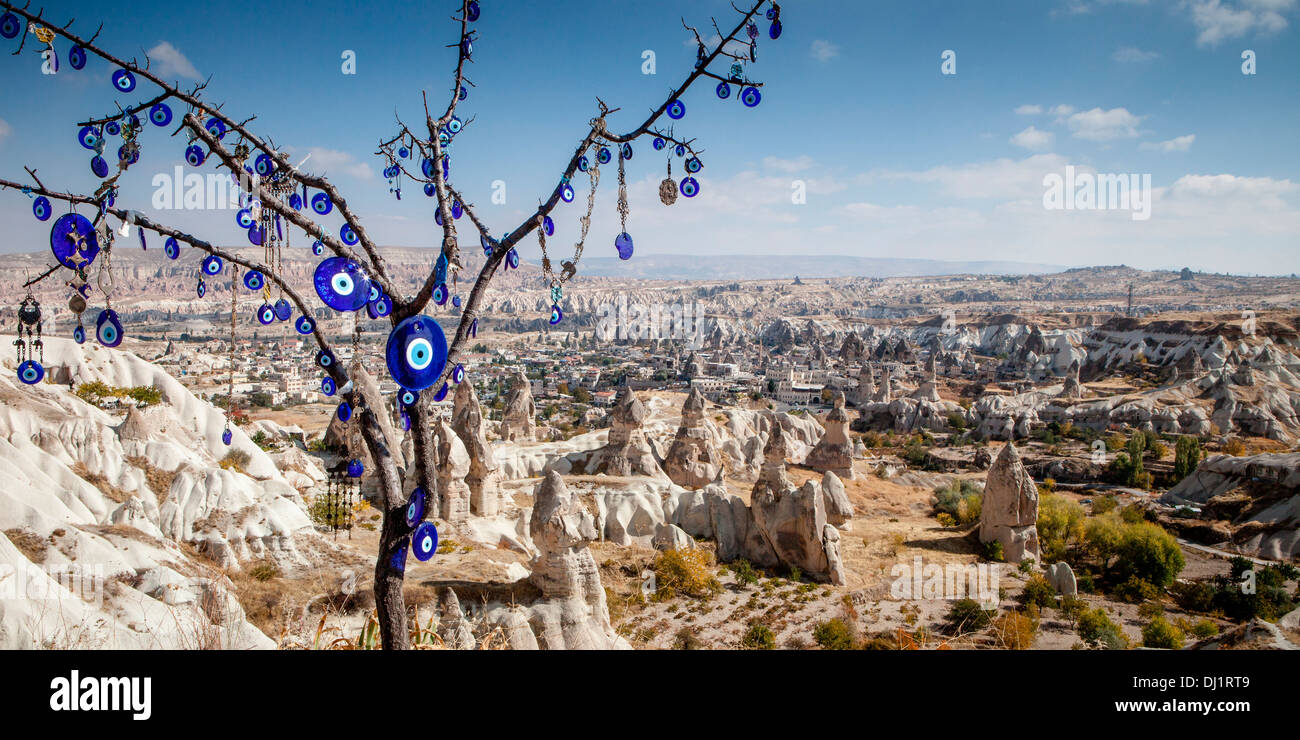 Cerulean blue glass charms of the Evil Eye are displayed in a tree at a viewpoint overlooking Cappadocia in Anatolia, Stock Photo