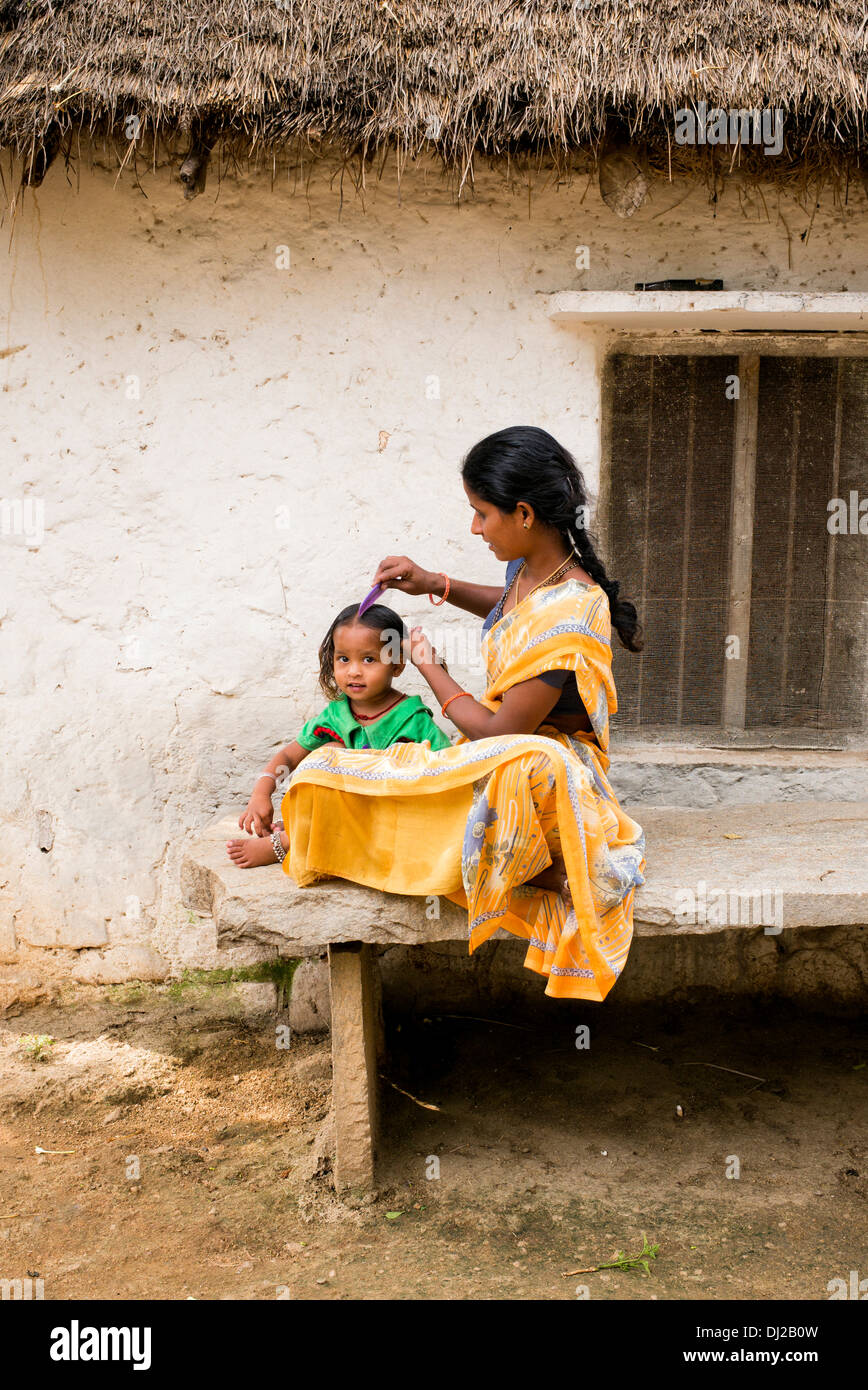 Indian mother combing her young daughters hair in a rural indian village. Andhra Pradesh, India - Stock Image