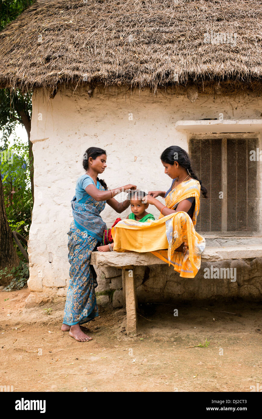 Indian mother and combing her young daughters hair in a rural indian village. Andhra Pradesh, India - Stock Image