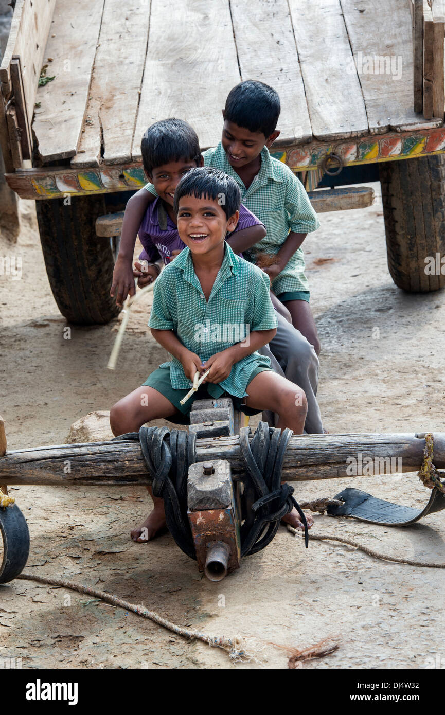 Young Indian boys playing with sticks on a bullock cart in a rural indian village. Andhra Pradesh, India - Stock Image