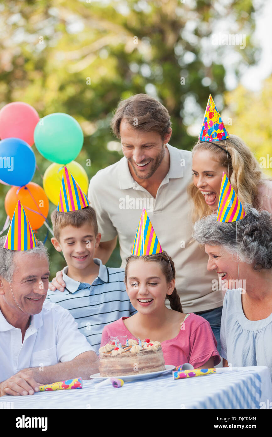 Cheerful family wearing party hat while celebrating birthday - Stock Image