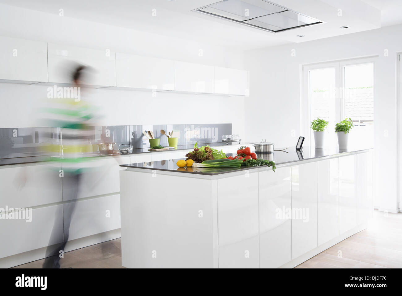 Germany, Cologne, Man in kitchen, blurred motion - Stock Image