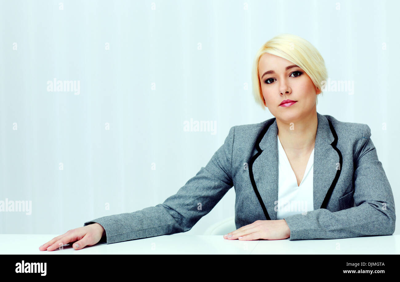 Portrait of a young pensive woman sitting at the table in office - Stock Image