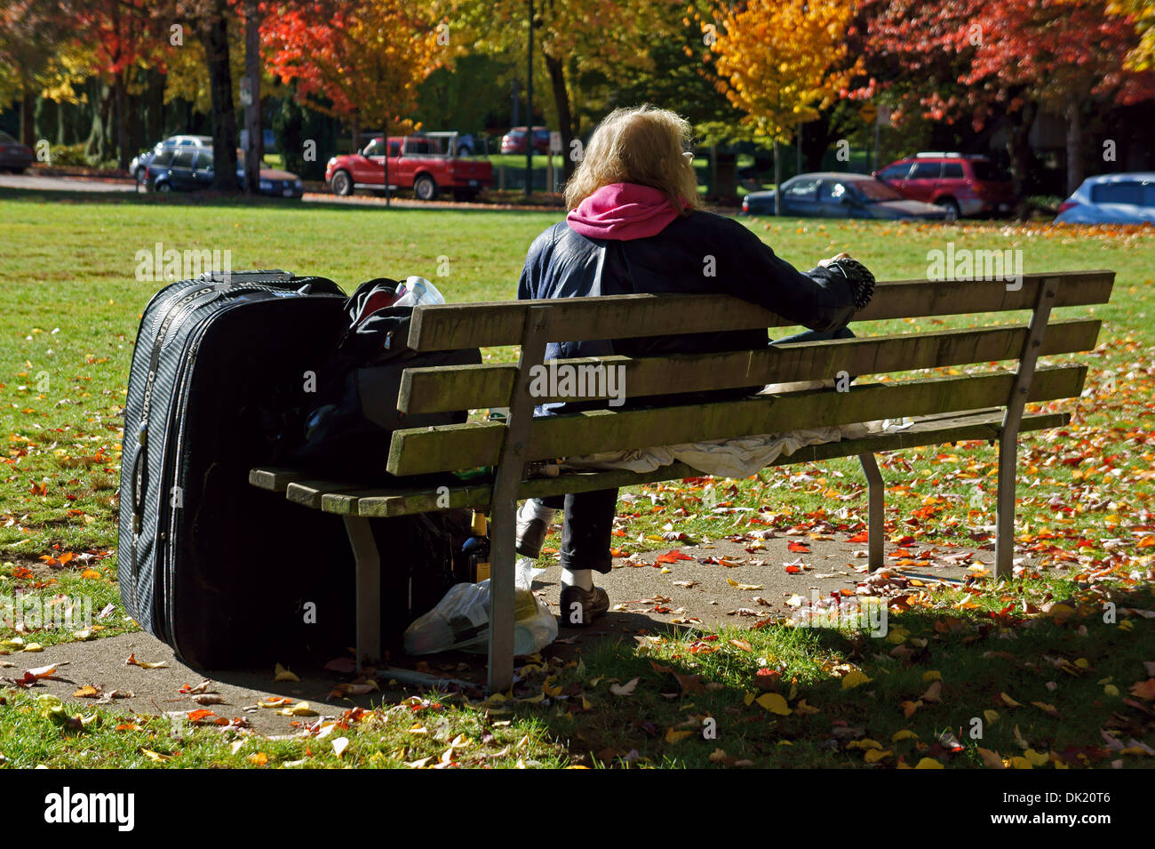homeless-senior-woman-sitting-on-a-park-
