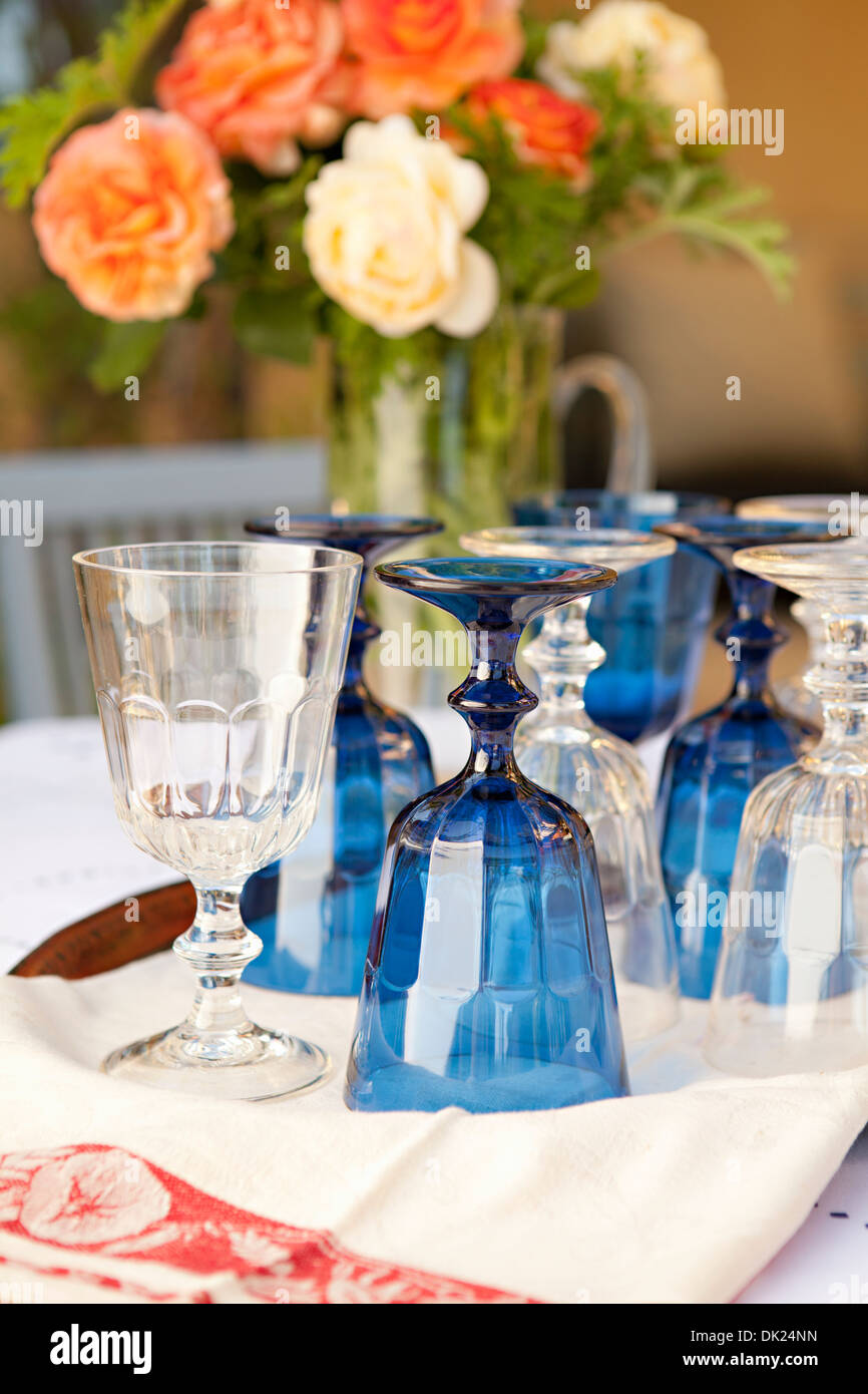 Water goblets for buffet on table with rose bouquet - Stock Image