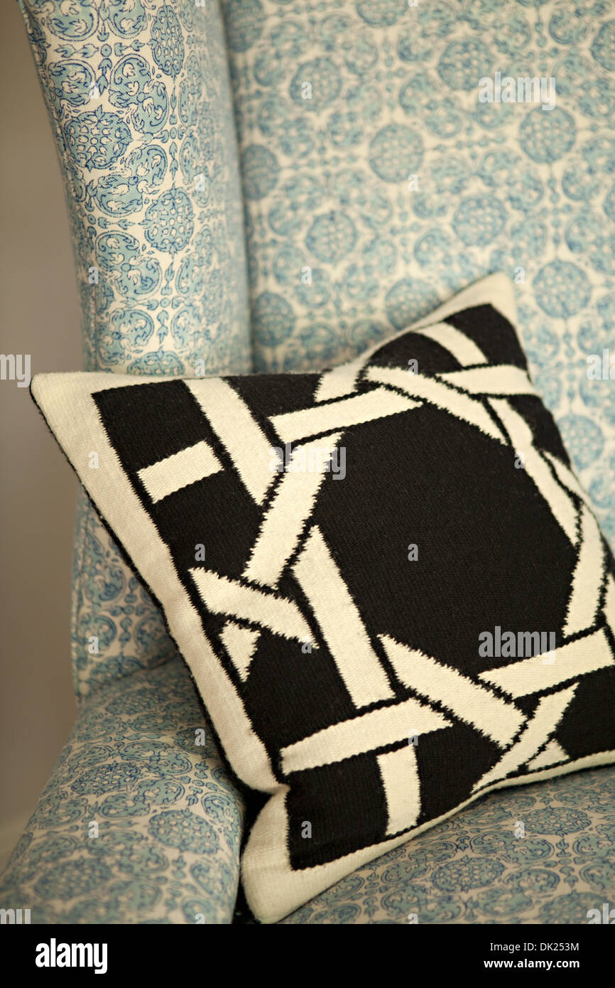 Close up of black and white needlepoint pillow on blue patterned wingback chair - Stock Image