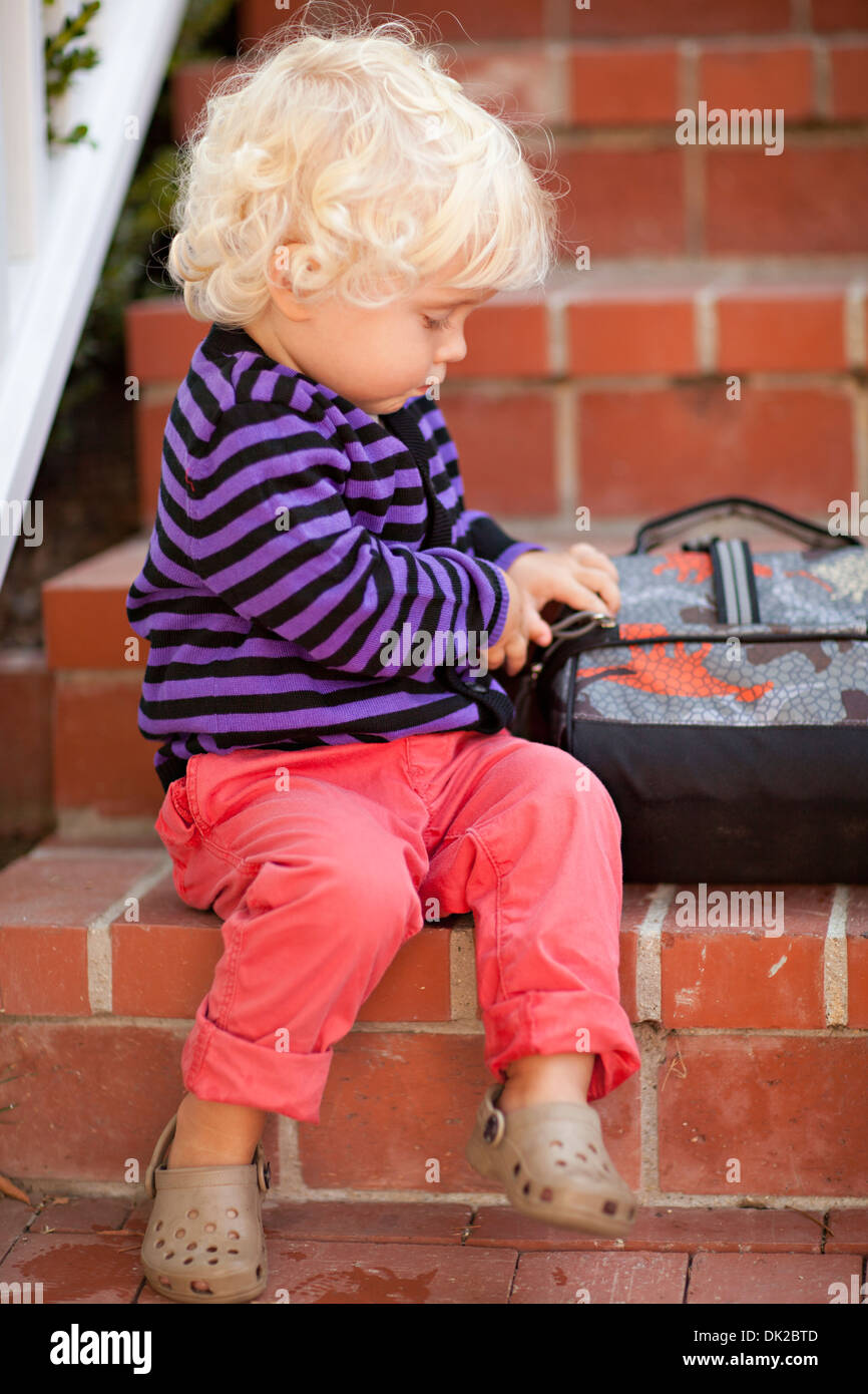 Blonde toddler school boy with curly hair with backpack on brick steps - Stock Image