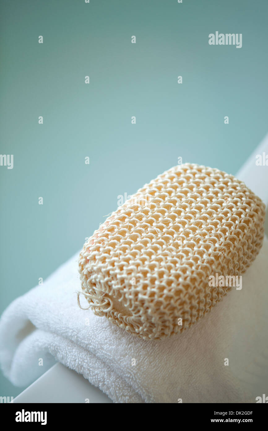 Close up high angle view of spa loofah on towel - Stock Image