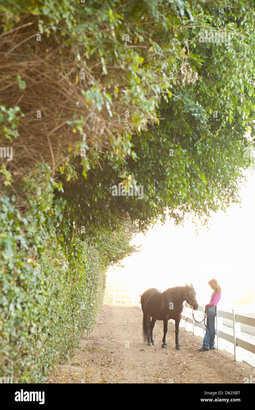 Woman with brown horse leaning against white fence on countryside path - Stock Image