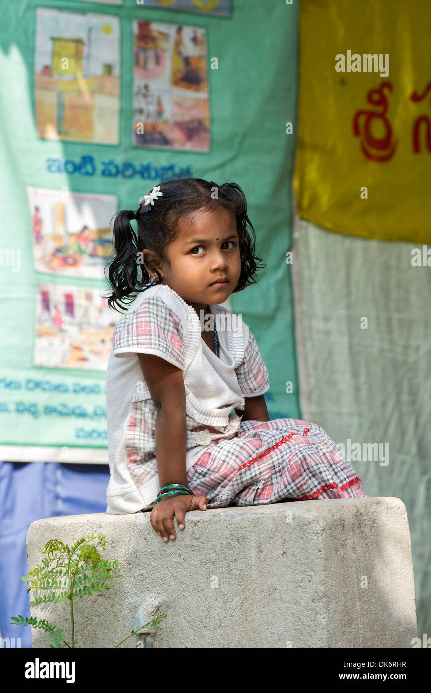 Young Indian girl sitting on a concrete post in a rural Indian village. Andhra Pradesh, India - Stock Image