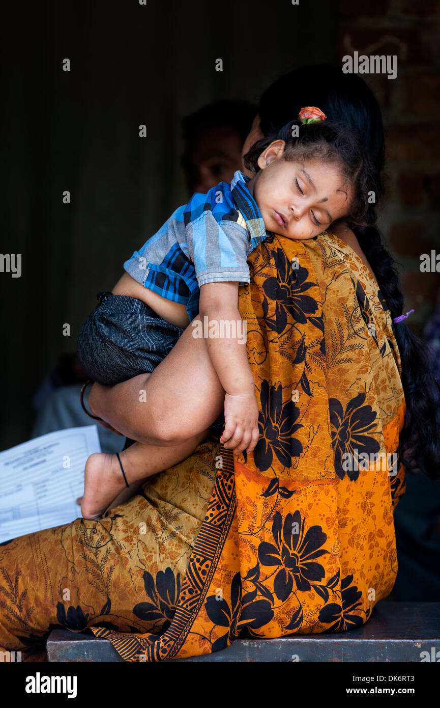 Young Indian baby girl sleeping on her mothers shoulder in a rural Indian village. Andhra Pradesh, India - Stock Image