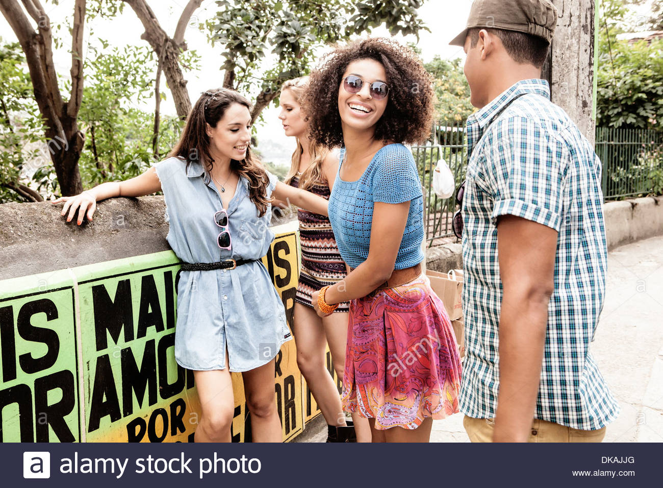 Four young people gathering outside park - Stock Image