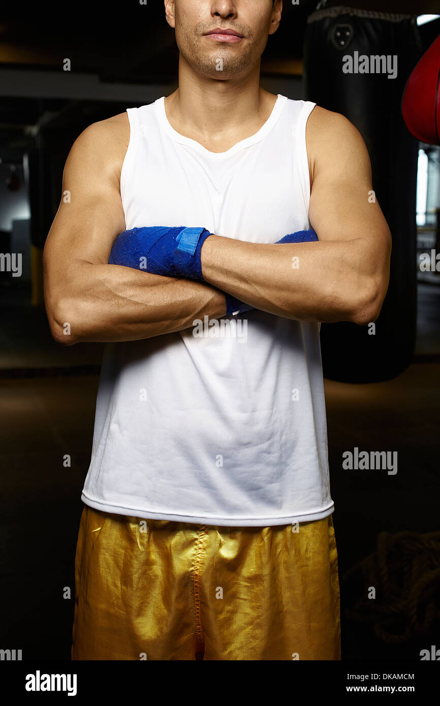 Cropped image of kickboxer with arms folded - Stock Image