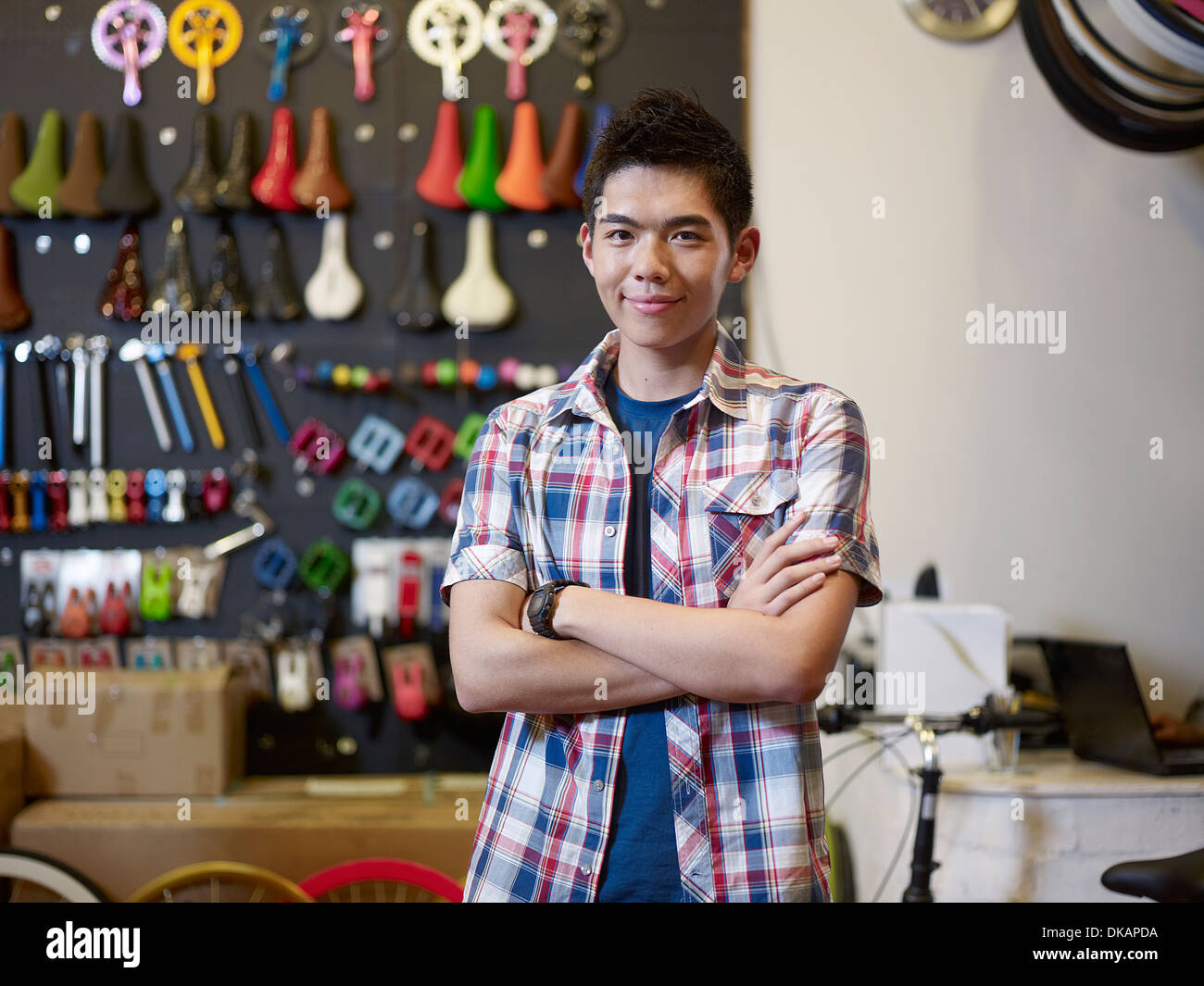 Portrait of young man in bike shop with arms folded - Stock Image