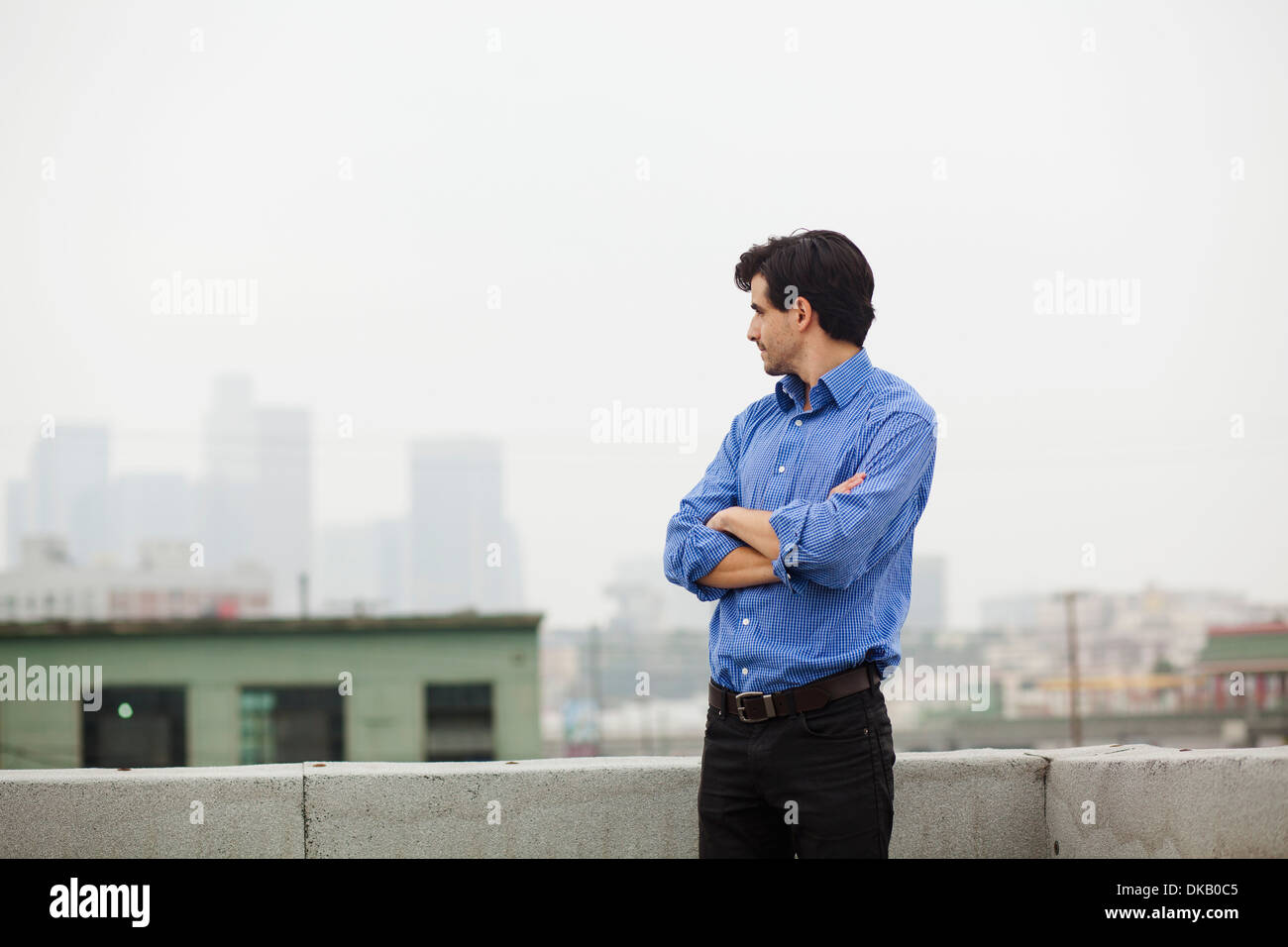 Young businessman with folded arms on city rooftop - Stock Image