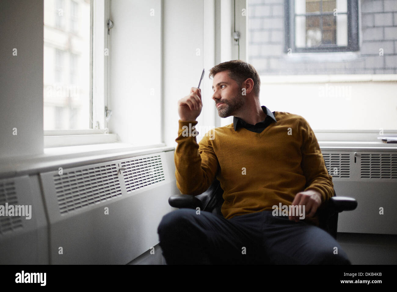 Casual businessman looking out of window - Stock Image