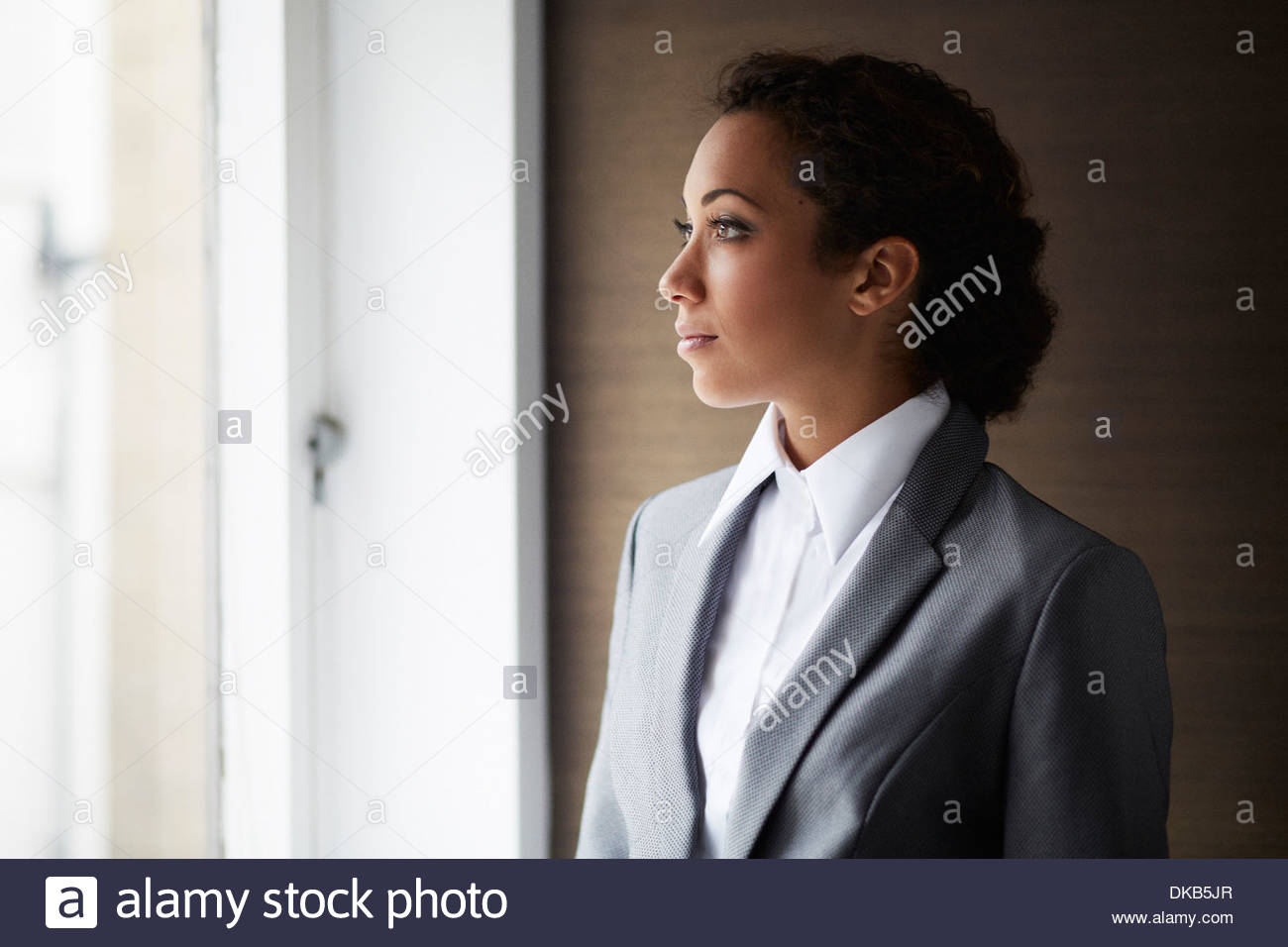 Portrait of businesswoman looking out of window - Stock Image