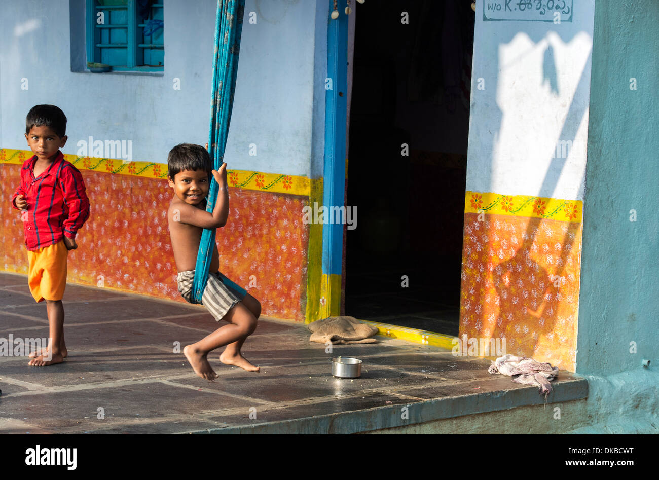 Young Indian boys playing on sari swings at home in a rural Indian village. Andhra Pradesh, India - Stock Image