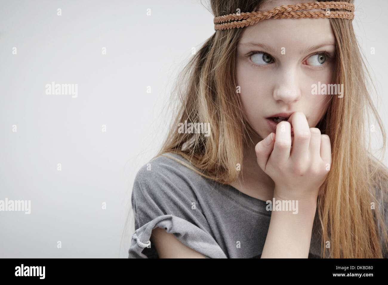 Portrait of girl wearing leather braid around head, holding feather, finger in mouth - Stock Image