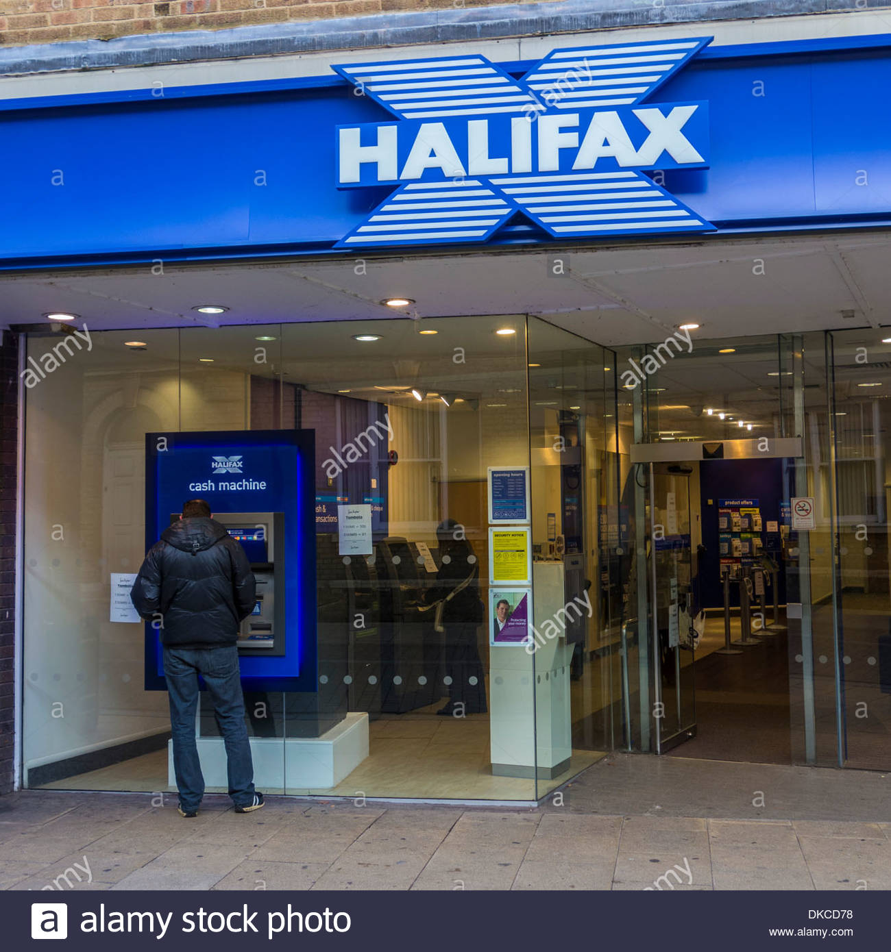 A customer uses a cash machine outside a branch of the Halifax bank, now part of Lloyds Bank Stock Photo