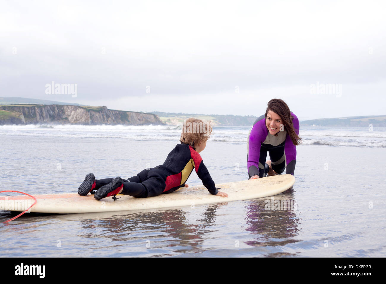 Mother teaching son how to surf - Stock Image