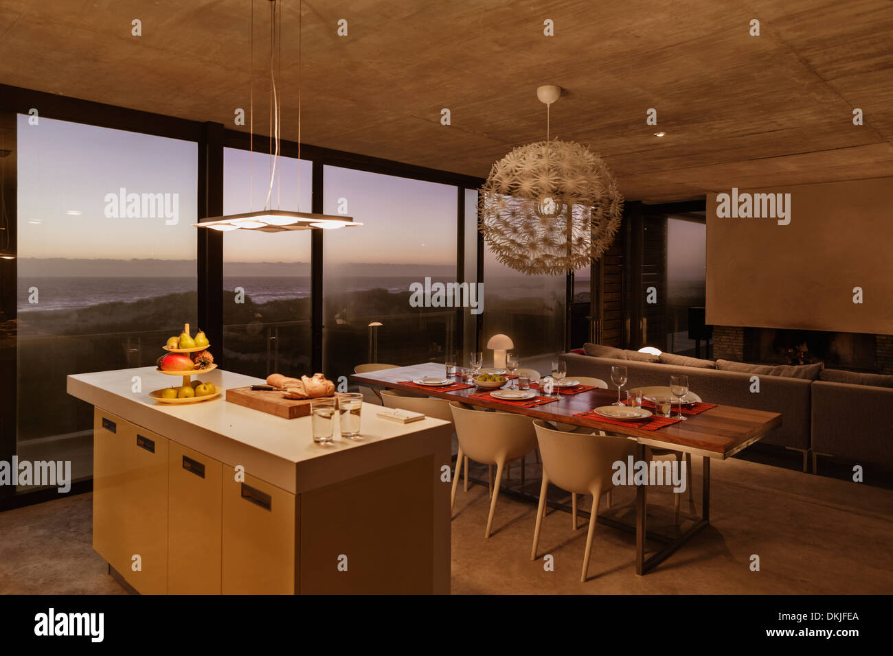 Breakfast Bar And Dining Table In Modern Kitchen Overlooking Ocean At Dusk