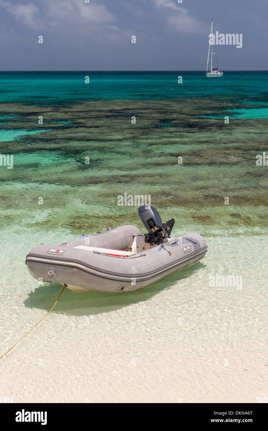 Dinghy on sand beach with coral underwater and yacht at anchor off Huon Island, Huon Atoll, New Caledonia, South - Stock Image