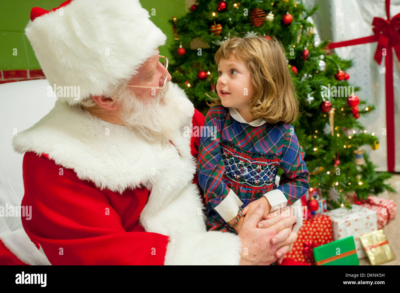 Santa Claus with a young girl  6 7 8 9 on his lap in a chair talking to him about what she wants for Christmas Stock Photo