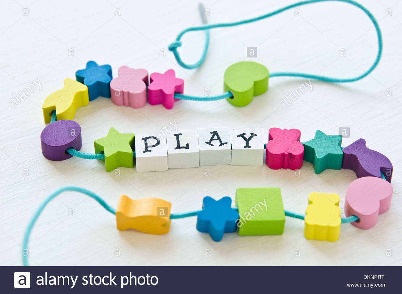 Toys beads strung together that spell 'play' on white background. - Stock Image